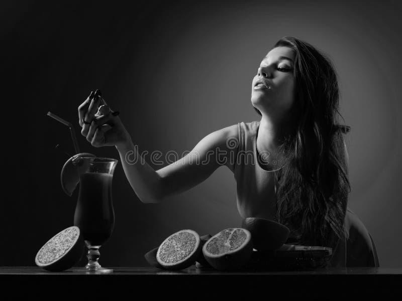 Menina bonita nova com vidro do cocktail Nascer do sol do Tequila do cocktail decorado com cereja e fatia de laranja imagem de stock