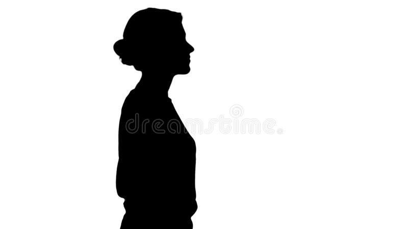 Menina bonita nova da silhueta com mãos no passeio dos bolsos fotografia de stock