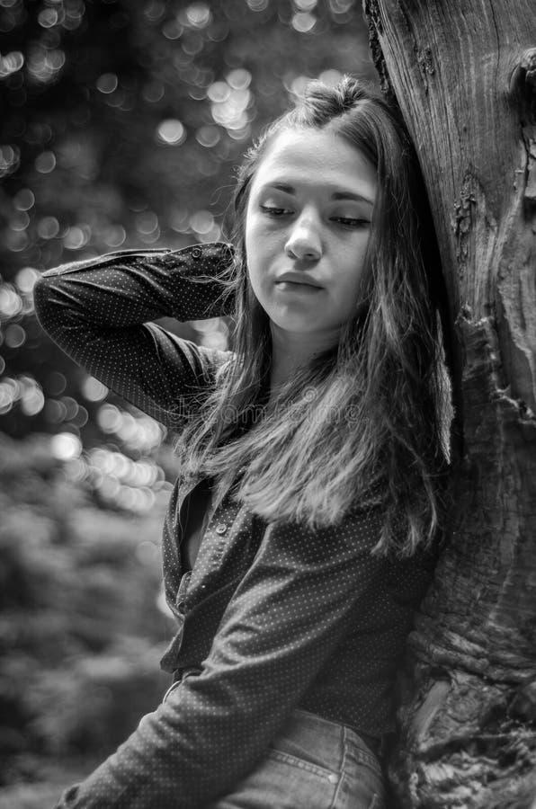 Menina bonita nova do adolescente com cabelo longo no short de uma camisa e da sarja de Nimes que descansa em uma árvore durante  imagem de stock royalty free