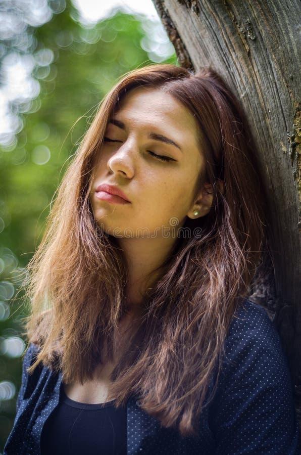 Menina bonita nova do adolescente com cabelo longo no short de uma camisa e da sarja de Nimes que descansa em uma árvore durante  imagens de stock