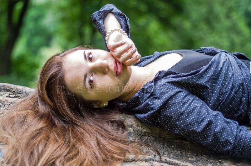 Menina bonita nova do adolescente com cabelo longo no short de uma camisa e da sarja de Nimes que descansa em uma árvore durante  imagens de stock royalty free