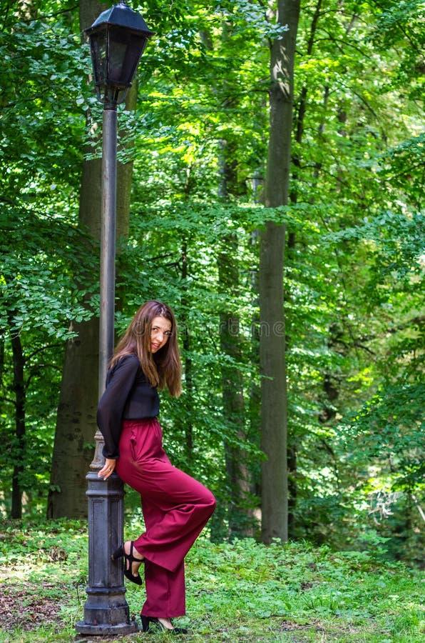 Menina bonita nova do adolescente com cabelo longo que anda no parque de Striysky em Lviv, levantando perto de uma lâmpada para i fotografia de stock