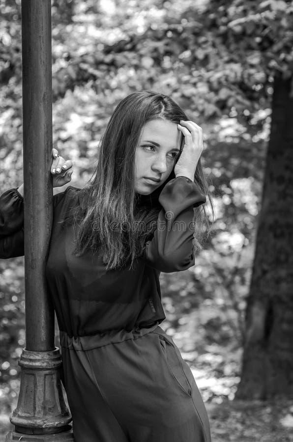 Menina bonita nova do adolescente com cabelo longo que anda no parque de Striysky em Lviv, levantando perto de uma lâmpada para i fotografia de stock royalty free
