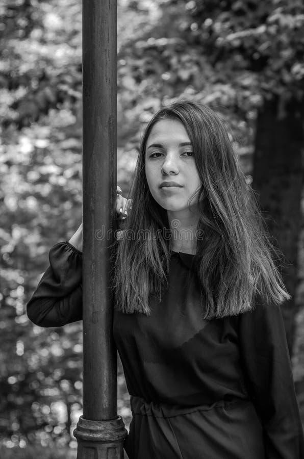 Menina bonita nova do adolescente com cabelo longo que anda no parque de Striysky em Lviv, levantando perto de uma lâmpada para i imagens de stock