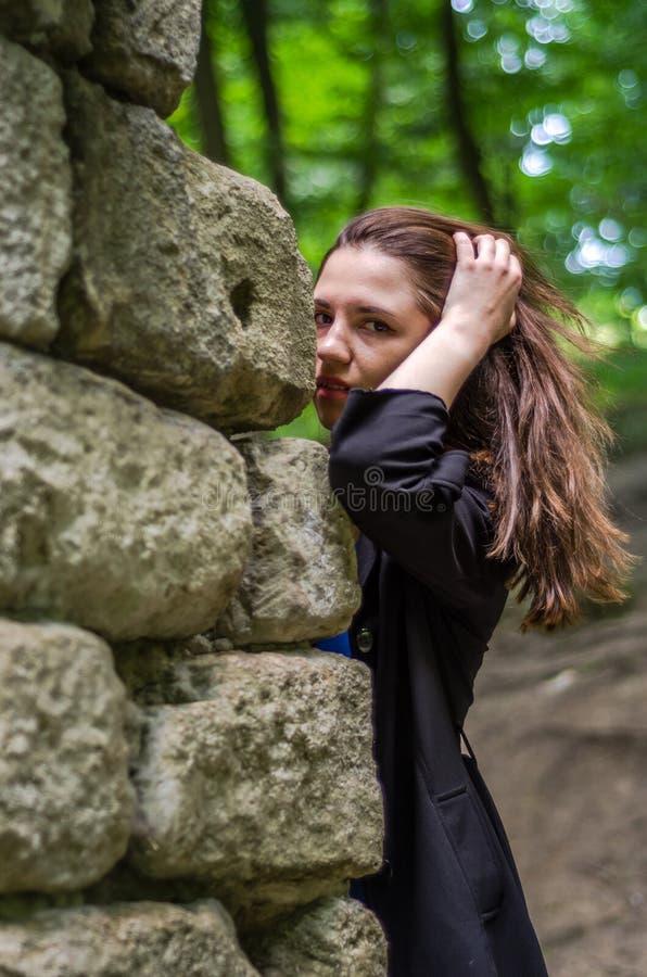 Menina bonita nova do adolescente em um casaco escuro e em um cabelo longo que olha atrás das ruínas de uma parede de pedra do ca fotografia de stock royalty free