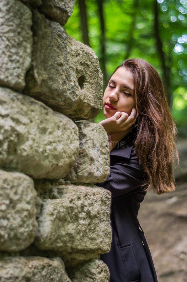 Menina bonita nova do adolescente em um casaco escuro e em um cabelo longo que olha atrás das ruínas de uma parede de pedra do ca fotos de stock