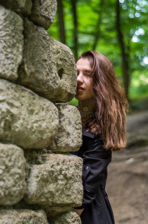 Menina bonita nova do adolescente em um casaco escuro e em um cabelo longo que olha atrás das ruínas de uma parede de pedra do ca imagens de stock