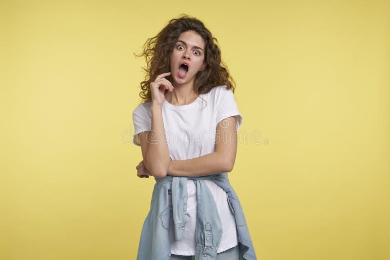 Menina bonita nova do estudante entusiasmado, abriu seus boca e olhos em uma surpresa, contra o fundo amarelo foto de stock