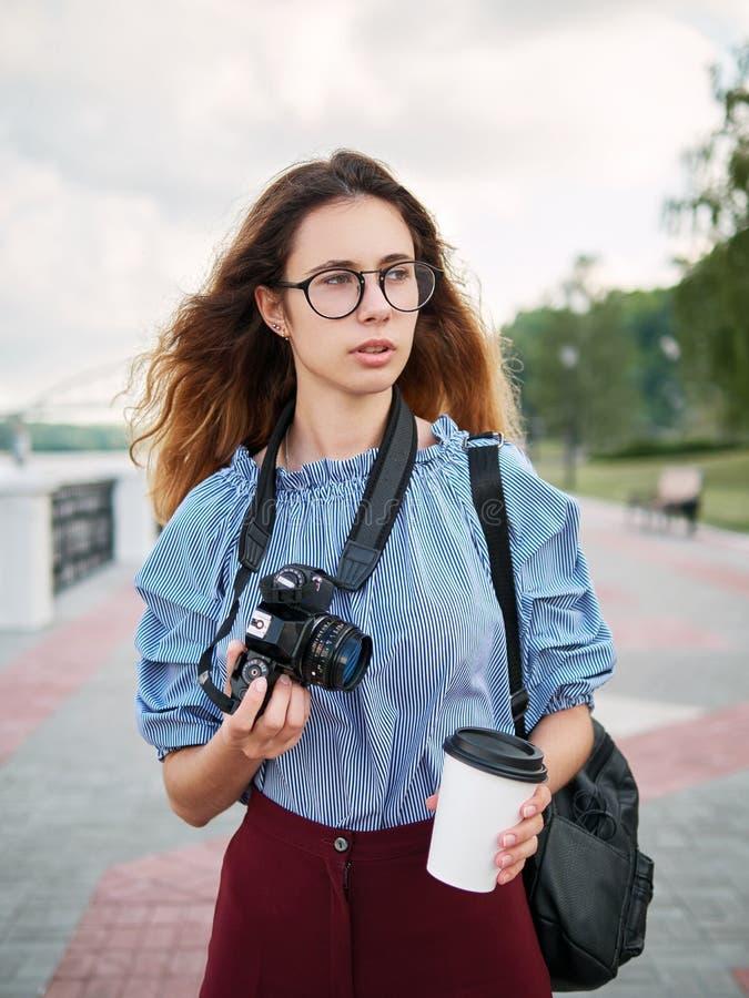 Menina bonita nova do estudante na blusa azul e nos vidros na moda que têm o divertimento com a câmera da xícara de café e da fot fotografia de stock