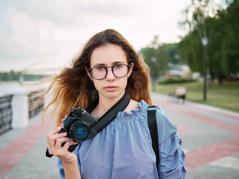 Menina bonita nova do estudante na blusa azul e nos vidros na moda que têm o divertimento com a câmera da xícara de café e da fot imagens de stock royalty free