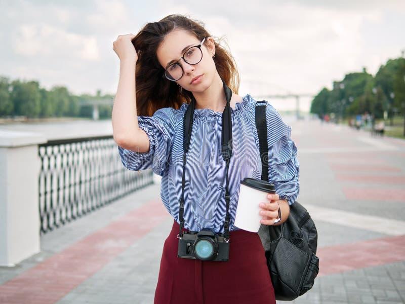 Menina bonita nova do estudante na blusa azul e nos vidros na moda que têm o divertimento com a câmera da xícara de café e da fot foto de stock royalty free