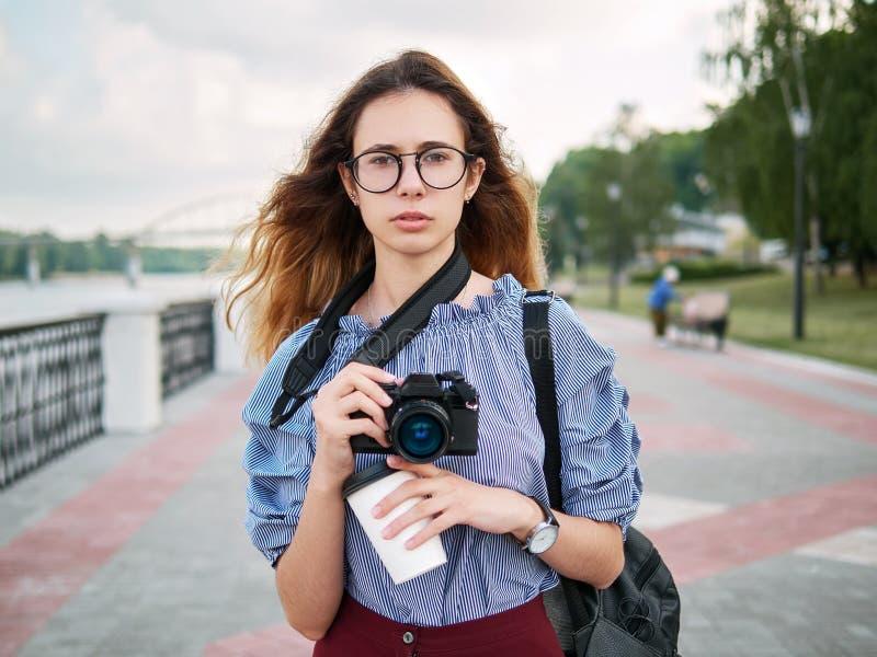 Menina bonita nova do estudante na blusa azul e nos vidros na moda que têm o divertimento com a câmera da xícara de café e da fot imagem de stock royalty free