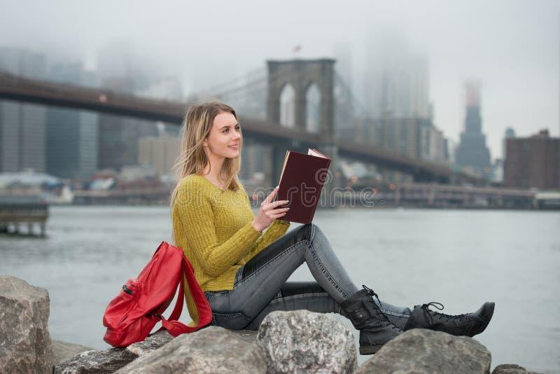 Menina bonita nova do estudante que lê um livro que senta-se perto da skyline de New York City fotografia de stock royalty free