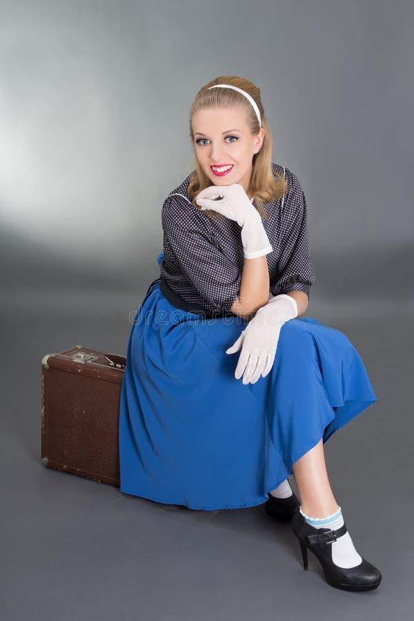 Menina bonita nova do pinup que senta-se na mala de viagem retro sobre o cinza imagem de stock