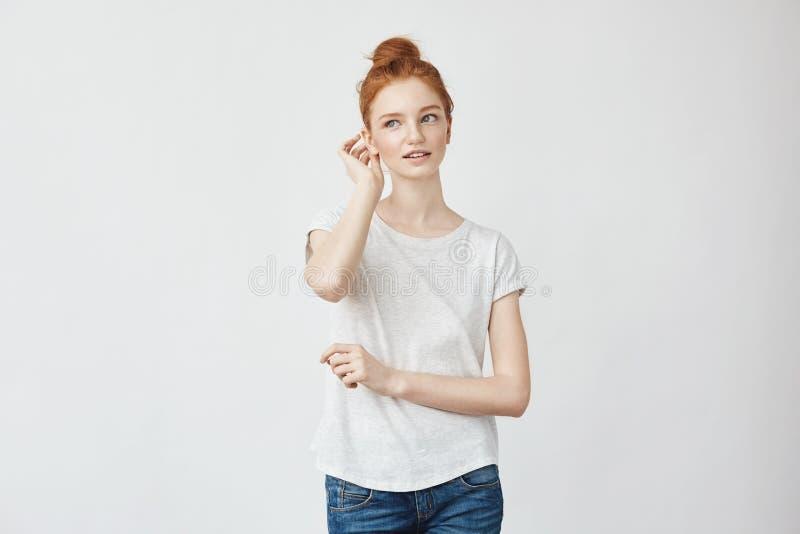 Menina bonita nova do ruivo que sorri corrigindo o cabelo fotografia de stock