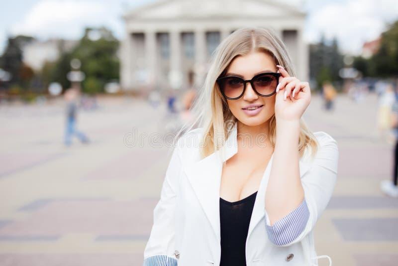 Menina bonita nova em óculos de sol à moda na rua da cidade foto de stock