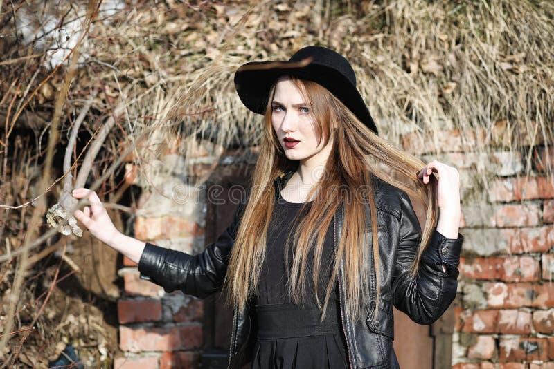 Menina bonita nova em um chapéu e com uma composição escura fora g foto de stock