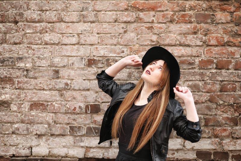 Menina bonita nova em um chapéu e com uma composição escura fora g imagens de stock