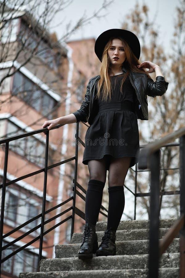 Menina bonita nova em um chapéu e com uma composição escura fora g imagem de stock