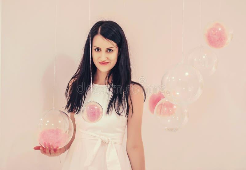 Menina bonita nova em um vestido branco em uma luz - fundo cor-de-rosa de balões transparentes com um enchimento cor-de-rosa fotografia de stock royalty free