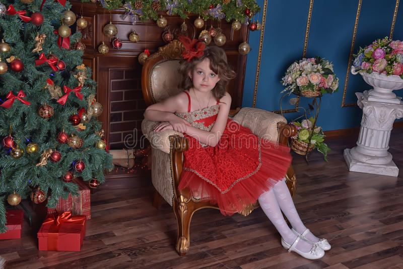 Menina bonita nova em um vestido vermelho ao lado da chaminé no Natal fotos de stock