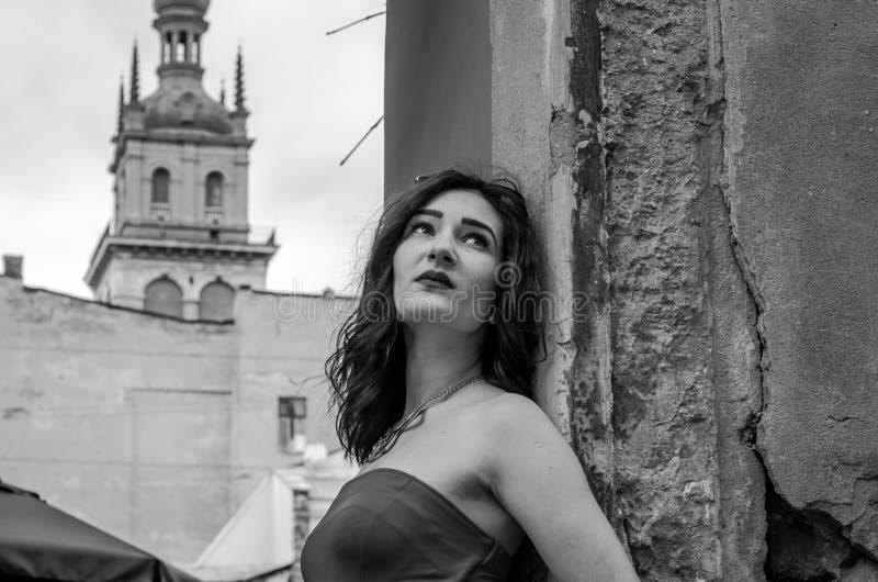 A menina bonita nova em um vestido vermelho dá uma volta através das ruas antigas da cidade de Lviv fotografia de stock