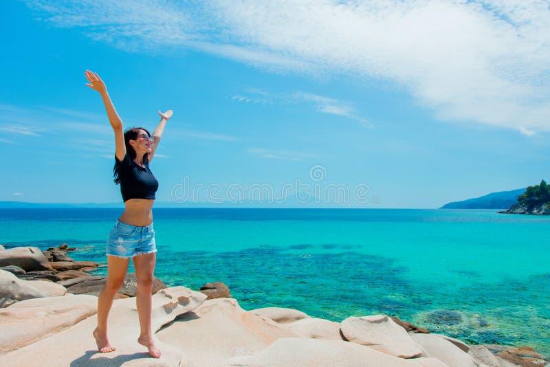 Menina bonita nova em uma rocha perto de uma costa de mar foto de stock