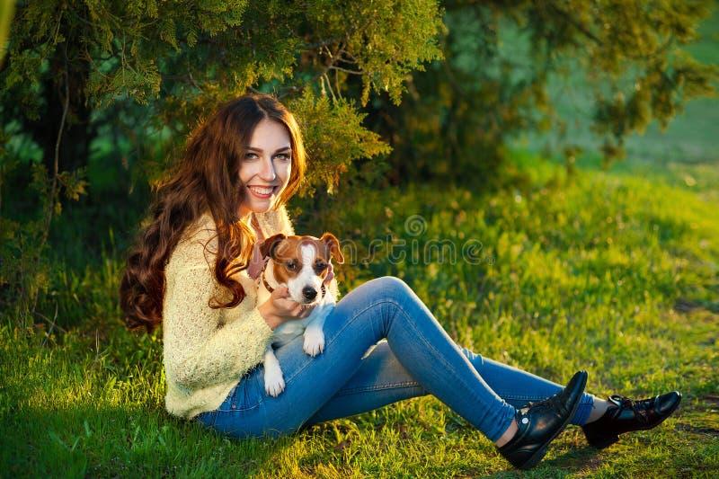 A menina bonita nova está morrendo e senta-se com seu animal de estimação Jack Russell Terrier na grama verde imagens de stock royalty free