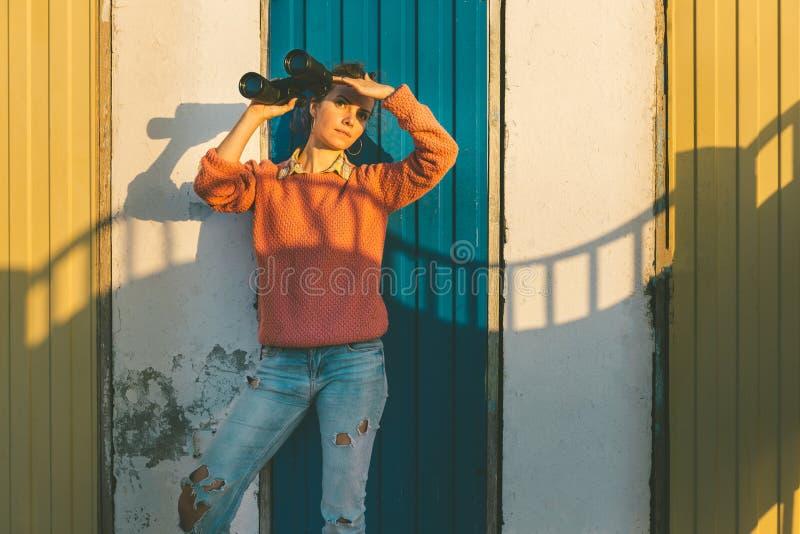 A menina bonita nova está perto da parede colorida com binóculos à disposição e olhando fixamente na distância Escuteiro Travel C fotos de stock