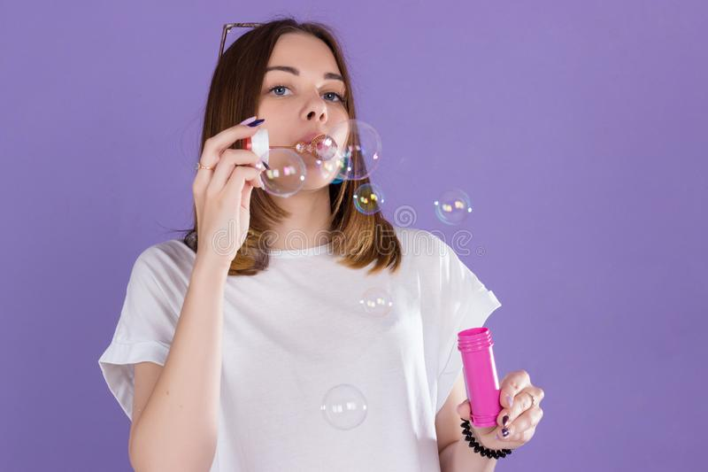 A menina bonita nova funde bolhas de sabão, estúdio fotografia de stock royalty free