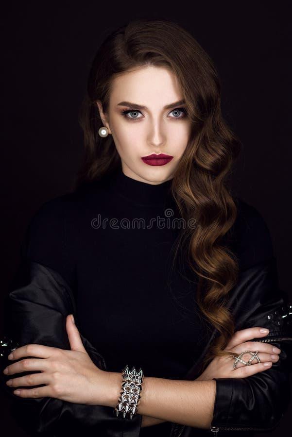 Menina bonita nova glamoroso do estilo da rocha no casaco de cabedal preto com os acessórios na obscuridade - fundo cinzento fotografia de stock royalty free