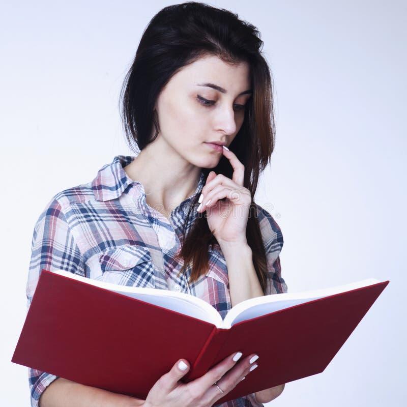 Menina bonita nova intdoors de leitura educação de um livro, auto de foto de stock royalty free