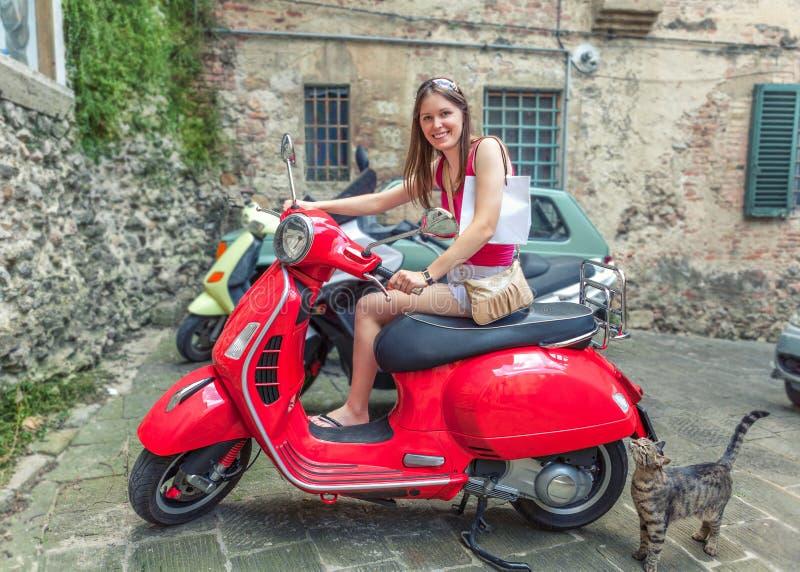 A menina bonita nova monta um Vespa vermelho do 'trotinette' de motor através das ruas de Roma, Itália fotos de stock royalty free