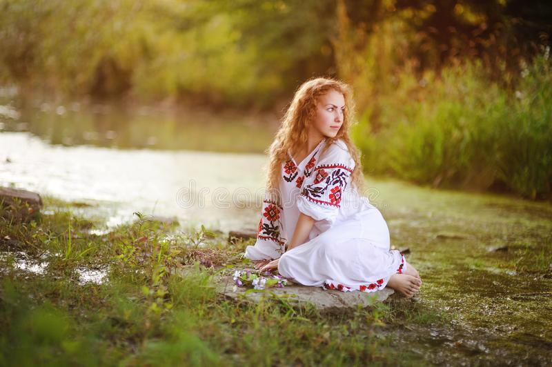Menina bonita nova na camisa branca com o ornamento floral que senta-se no banco de rio foto de stock