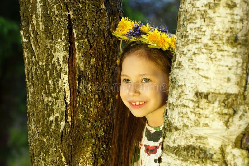 A menina bonita nova na grinalda das flores está olhando fora da árvore de vidoeiro imagem de stock
