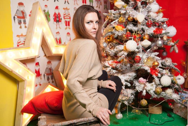 Menina bonita nova nas decorações do ano novo no fundo do papel de parede com povos coloridos foto de stock royalty free