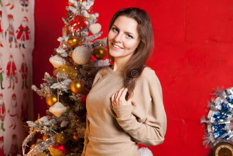 Menina bonita nova nas decorações do ano novo no fundo do papel de parede com povos coloridos fotografia de stock