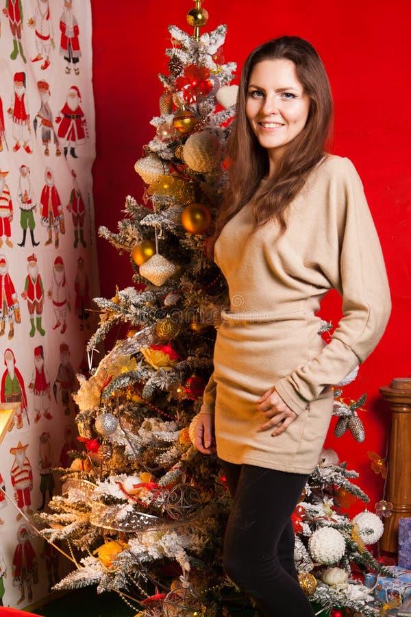 Menina bonita nova nas decorações do ano novo no fundo do papel de parede com povos coloridos fotografia de stock royalty free