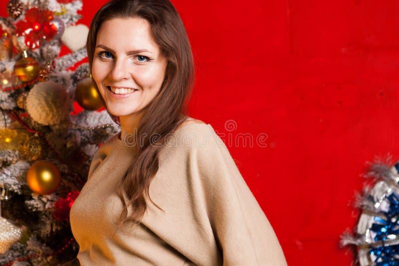 Menina bonita nova nas decorações do ano novo no fundo vermelho imagens de stock royalty free