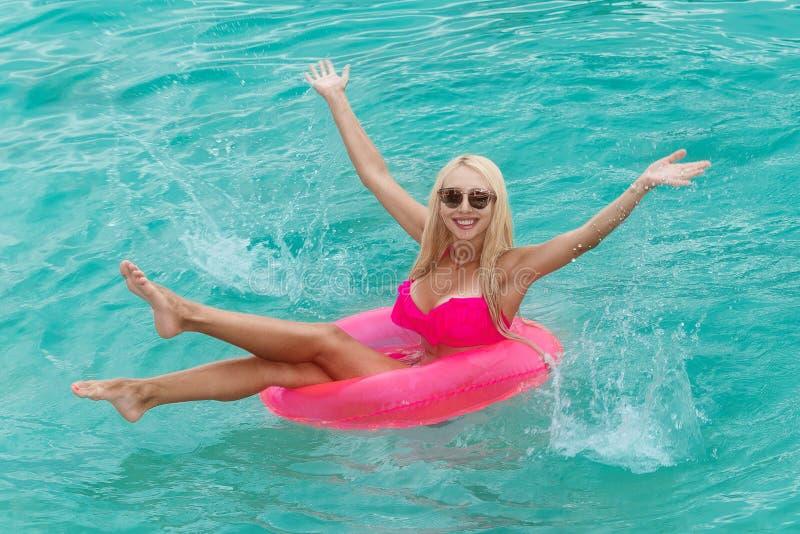 A menina bonita nova no biquini nada em um mar tropical em um rubb imagem de stock royalty free