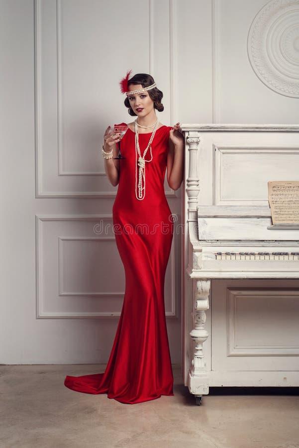 Menina bonita nova no estilo vermelho do vestido 20 do ` s ou 30 ` s com vidro de martini perto do piano Mulher bonita do estilo  imagens de stock