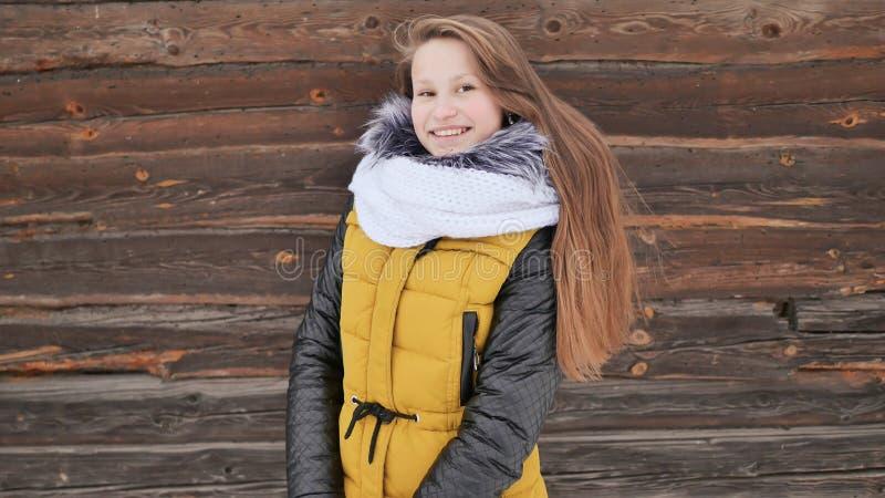 A menina bonita nova no inverno veste o levantamento positivamente na câmera no fundo de uma casa de madeira no fotos de stock royalty free