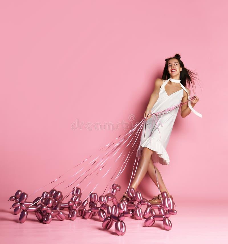 A menina bonita nova no vestido branco anda os cães infláveis do balão em um sorriso feliz da trela fotos de stock royalty free