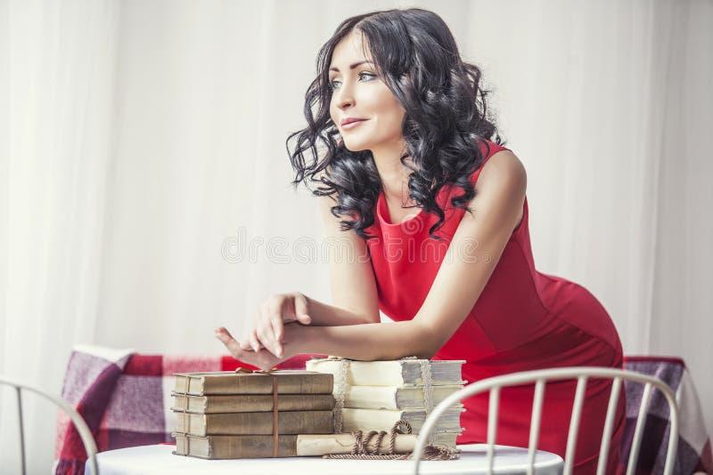Menina bonita nova no vestido vermelho com os livros na tabela fotos de stock
