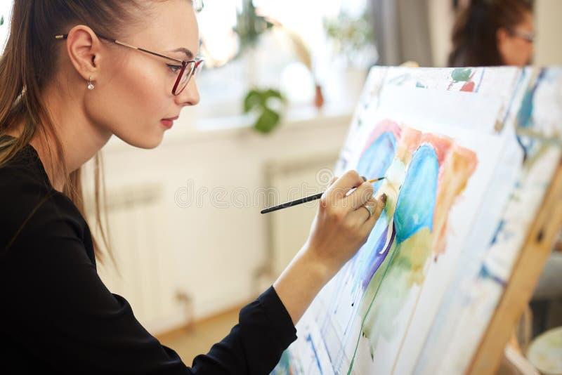 A menina bonita nova nos vidros vestidos na blusa preta senta-se na arma??o e pinta-se uma imagem na escola de tiragem fotografia de stock royalty free