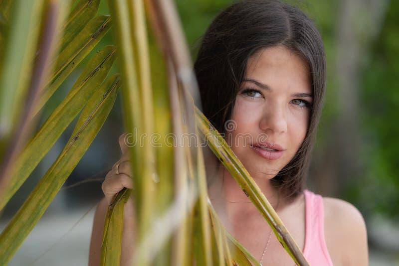 A menina bonita nova olha através de uma grande folha de uma palmeira imagens de stock