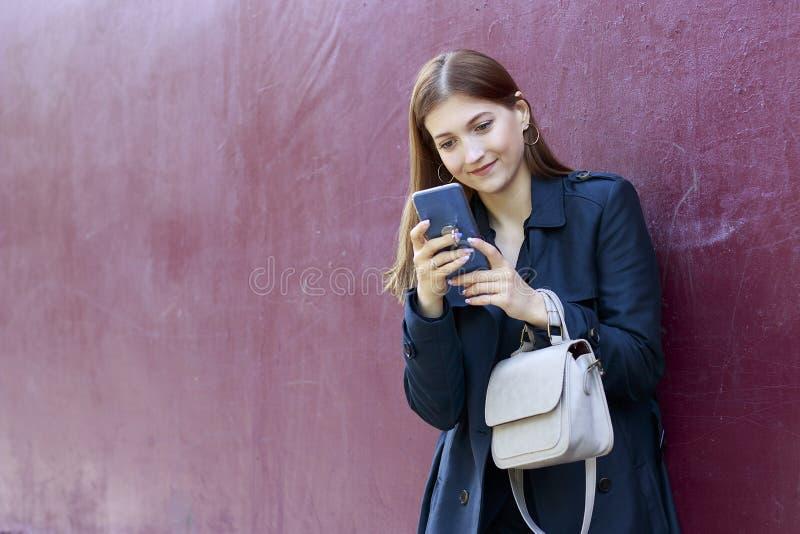 A menina bonita nova olha no smartphone, fundo cor-de-rosa imagens de stock