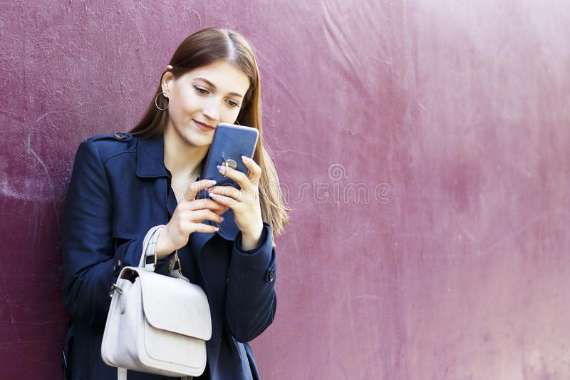 A menina bonita nova olha no smartphone, fundo cor-de-rosa imagem de stock