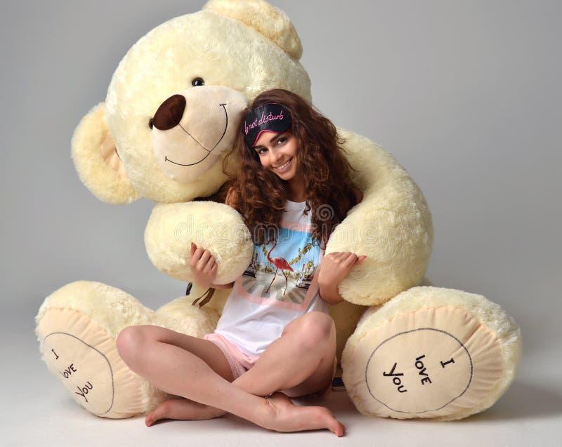 Menina bonita nova que abraça o smili feliz do brinquedo macio grande do urso de peluche imagem de stock royalty free