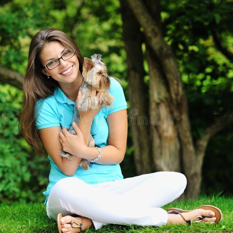 Menina bonita nova que abraça seu cão pequeno perto de um copyspace imagens de stock royalty free